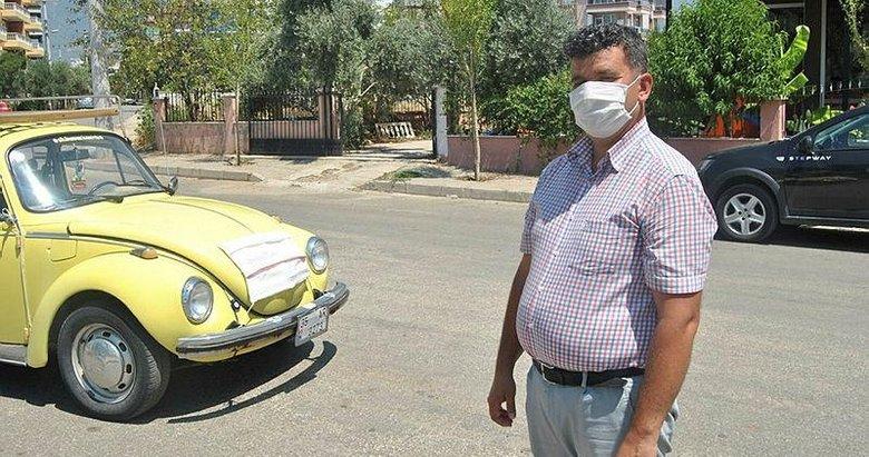 Kovid-19 tedbirlerine dikkati çekmek için arabasına maske taktı